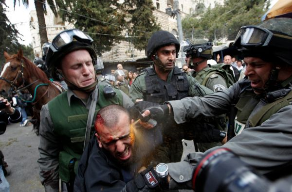Israeli border police officers use pepper spray as they detain an injured Palestinian protester during clashes on Land Day in March