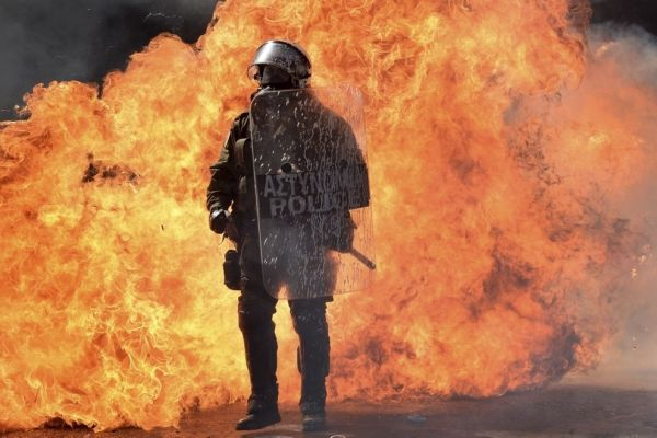 A police officer stands in front of a wall of flames during a protest in Athens